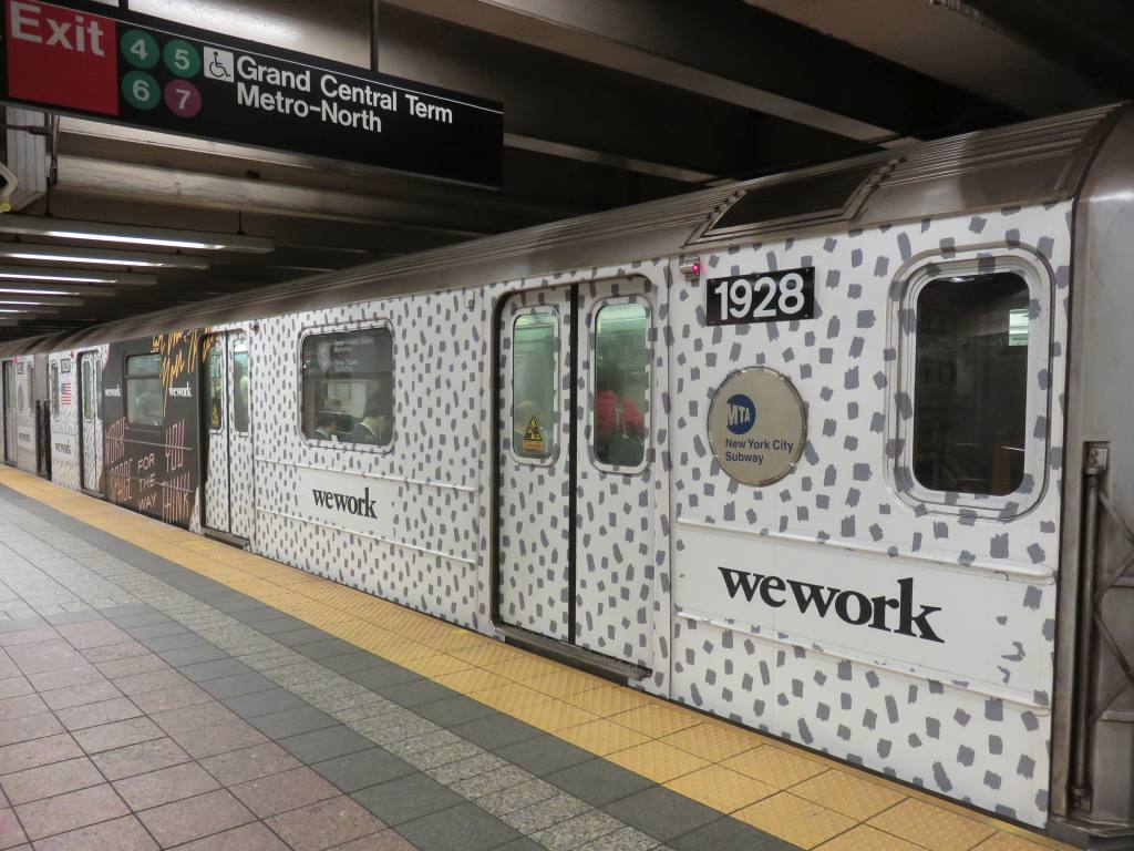 (132k, 1024x768)<br><b>Country:</b> United States<br><b>City:</b> New York<br><b>System:</b> New York City Transit<br><b>Line:</b> IRT Times Square-Grand Central Shuttle<br><b>Location:</b> Grand Central <br><b>Route:</b> S<br><b>Car:</b> R-62A (Bombardier, 1984-1987)  1928 <br><b>Photo by:</b> Robbie Rosenfeld<br><b>Date:</b> 9/6/2017<br><b>Notes:</b> WeWork ad wrap<br><b>Viewed (this week/total):</b> 0 / 421