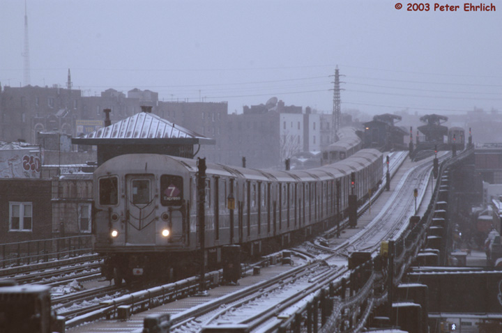(110k, 720x478)<br><b>Country:</b> United States<br><b>City:</b> New York<br><b>System:</b> New York City Transit<br><b>Line:</b> IRT Flushing Line<br><b>Location:</b> 69th Street/Fisk Avenue <br><b>Route:</b> 7<br><b>Car:</b> R-62A (Bombardier, 1984-1987)  1681 <br><b>Photo by:</b> Peter Ehrlich<br><b>Date:</b> 3/6/2003<br><b>Notes:</b> Triple R62A scene in the snow.  1681 is leading a Flushing line express, which is about to pass 69th Street/Fisk Avenue station. A Flushing-bound local and an inbound train are visible at Woodside station.<br><b>Viewed (this week/total):</b> 1 / 5658