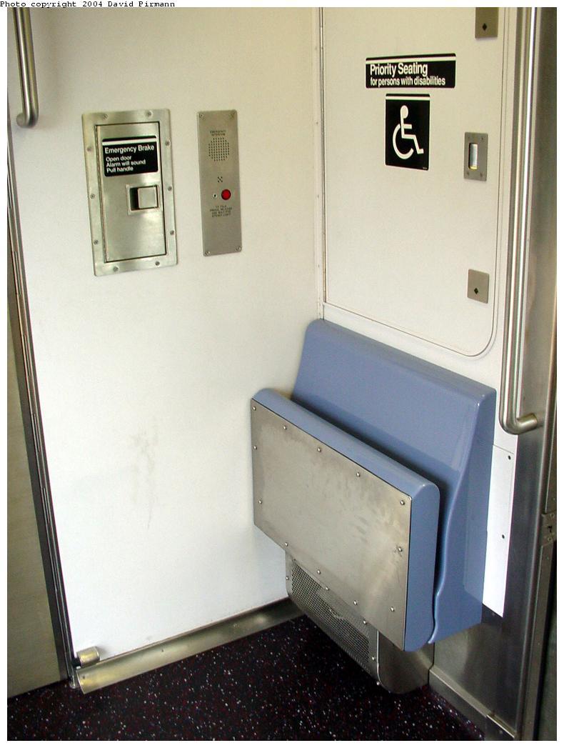(96k, 790x1047)<br><b>Country:</b> United States<br><b>City:</b> New York<br><b>System:</b> New York City Transit<br><b>Car:</b> R-142 or R-142A (Number Unknown) Interior <br><b>Photo by:</b> David Pirmann<br><b>Date:</b> 7/29/2000<br><b>Notes:</b> Interior showing car end- flip down seats, intercom, emergency brake cover<br><b>Viewed (this week/total):</b> 0 / 4225
