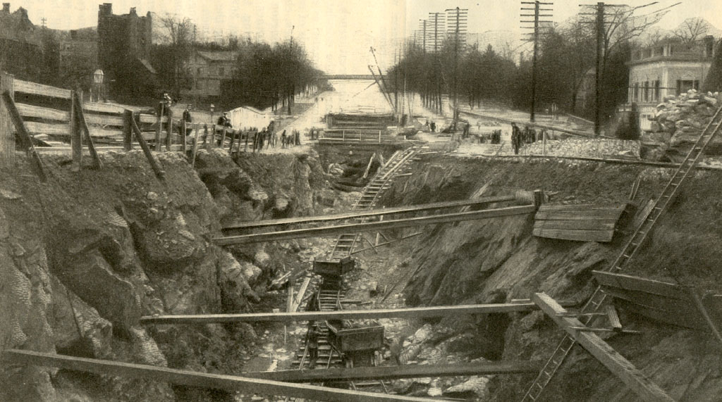 (172k, 1024x571)<br><b>Country:</b> United States<br><b>City:</b> New York<br><b>System:</b> New York City Transit<br><b>Photo by:</b> Munsey's Magazine, 1902 <br><b>Notes:</b> View of the work on Broadway, looking south from One Hundred and Fifty Seventh Street, toward Trinity Church Cemetery. Both north and south of this point are hills through which a tunnel is being driven, the northern tunnel being nearly two miles long.<br><b>Viewed (this week/total):</b> 2 / 5631