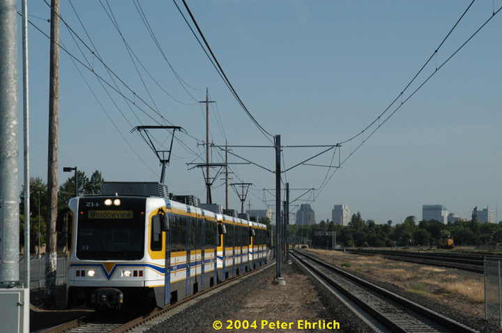 (129k, 720x478)<br><b>Country:</b> United States<br><b>City:</b> Sacramento, CA<br><b>System:</b> SACRT Light Rail<br><b>Location:</b> City College <br><b>Car:</b> Sacramento CAF LRV  214 <br><b>Photo by:</b> Peter Ehrlich<br><b>Date:</b> 6/28/2004<br><b>Notes:</b> A 3-car outbound train approaching City College Station, with the downtown skyline, and a Union Pacific locomotive, in the background.<br><b>Viewed (this week/total):</b> 0 / 1475