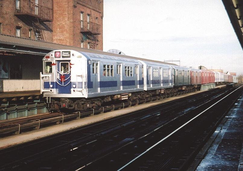 (208k, 805x566)<br><b>Country:</b> United States<br><b>City:</b> New York<br><b>System:</b> New York City Transit<br><b>Line:</b> IRT Flushing Line<br><b>Location:</b> 52nd Street/Lincoln Avenue <br><b>Route:</b> Fan Trip<br><b>Car:</b> R-33 Main Line (St. Louis, 1962-63) 9011 <br><b>Photo by:</b> Gary Chatterton<br><b>Date:</b> 11/28/2004<br><b>Notes:</b> R33/SMEE train of many colors in holiday 7 line service.<br><b>Viewed (this week/total):</b> 1 / 4143