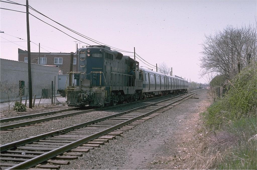 (248k, 1024x678)<br><b>Country:</b> United States<br><b>City:</b> New York<br><b>System:</b> New York City Transit<br><b>Car:</b> R-46 (Pullman-Standard, 1974-75)  <br><b>Photo by:</b> Steve Zabel<br><b>Collection of:</b> Joe Testagrose<br><b>Date:</b> 4/23/1975<br><b>Notes:</b> Bangor & Aroostook GP7/9 #62 delivering R46 cars via LIRR to Fresh Pond Yard.<br><b>Viewed (this week/total):</b> 3 / 3988