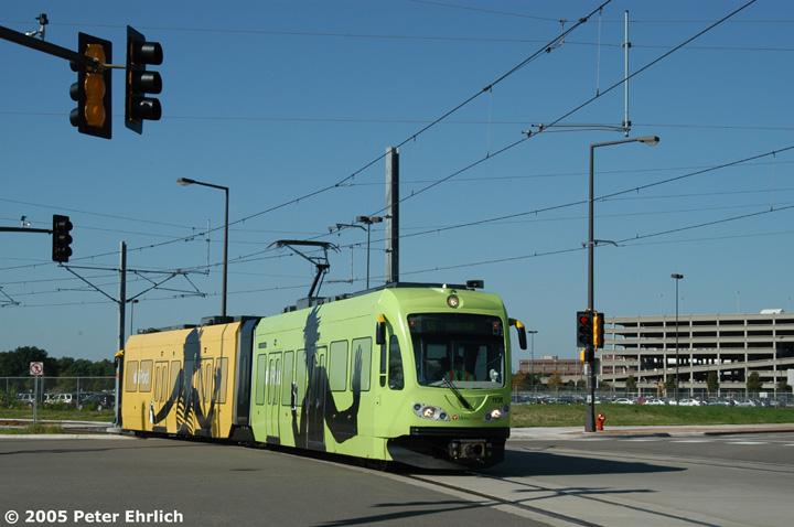 (120k, 720x478)<br><b>Country:</b> United States<br><b>City:</b> Minneapolis, MN<br><b>System:</b> MNDOT Light Rail Transit<br><b>Line:</b> Hiawatha Line<br><b>Location:</b> <b><u>28th Ave. </b></u><br><b>Car:</b> Bombardier Flexity Swift  110 <br><b>Photo by:</b> Peter Ehrlich<br><b>Date:</b> 8/27/2005<br><b>Notes:</b> Inbound train at the 28th Avenue/82nd Street intersection just beyond 28th Avenue Station.  110 is one of at least three LRVs shrinkwrapped with iPod adverts.<br><b>Viewed (this week/total):</b> 0 / 1692