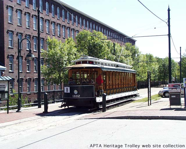 (81k, 640x512)<br><b>Country:</b> United States<br><b>City:</b> Lowell, MA<br><b>System:</b> National Streetcar Museum at Lowell <br><b>Car:</b> Gomaco Replica 1602 <br><b>Collection of:</b> APTA Heritage Trolley collection via Peter Ehrlich<br><b>Notes:</b> Lowell replica 15-bench Narragansett open car, one of 2 built, at Boott Mills building in Lowell.<br><b>Viewed (this week/total):</b> 1 / 2236
