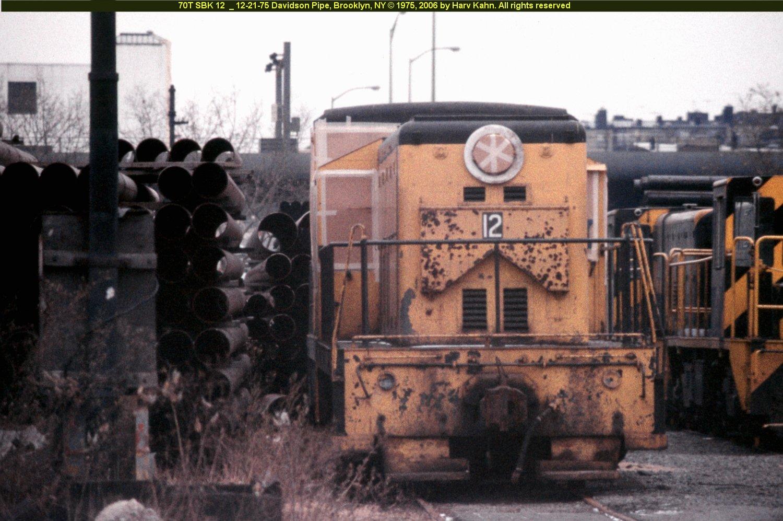 (262k, 1500x997)<br><b>Country:</b> United States<br><b>City:</b> New York<br><b>System:</b> New York City Transit<br><b>Location:</b> 39th Street, west of 3rd Avenue at Davidson's Pipe Works<br><b>Car:</b> GE 70T Locomotive (SBK)  12 <br><b>Photo by:</b> Harv Kahn<br><b>Date:</b> 12/21/1975<br><b>Viewed (this week/total):</b> 0 / 2522