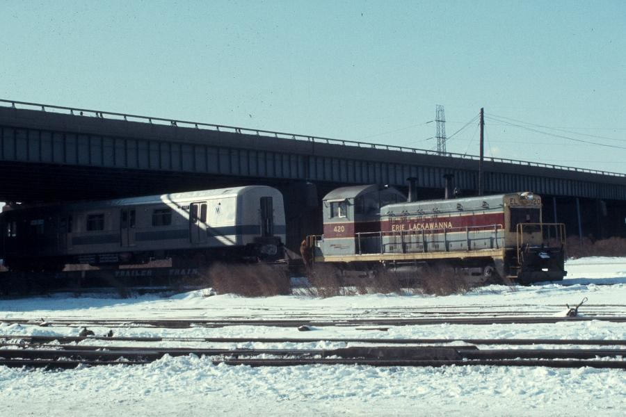(74k, 900x600)<br><b>Country:</b> United States<br><b>City:</b> Secaucus, NJ<br><b>System:</b> New York City Transit<br><b>Location:</b> Croxton Yard (NYCTA Equipment Delivery)<br><b>Car:</b> R-46 (Pullman-Standard, 1974-75) 557 <br><b>Photo by:</b> Harv Kahn<br><b>Date:</b> 2/7/1976<br><b>Notes:</b> With Eric-Lackawanna NW2 #420.<br><b>Viewed (this week/total):</b> 2 / 3500