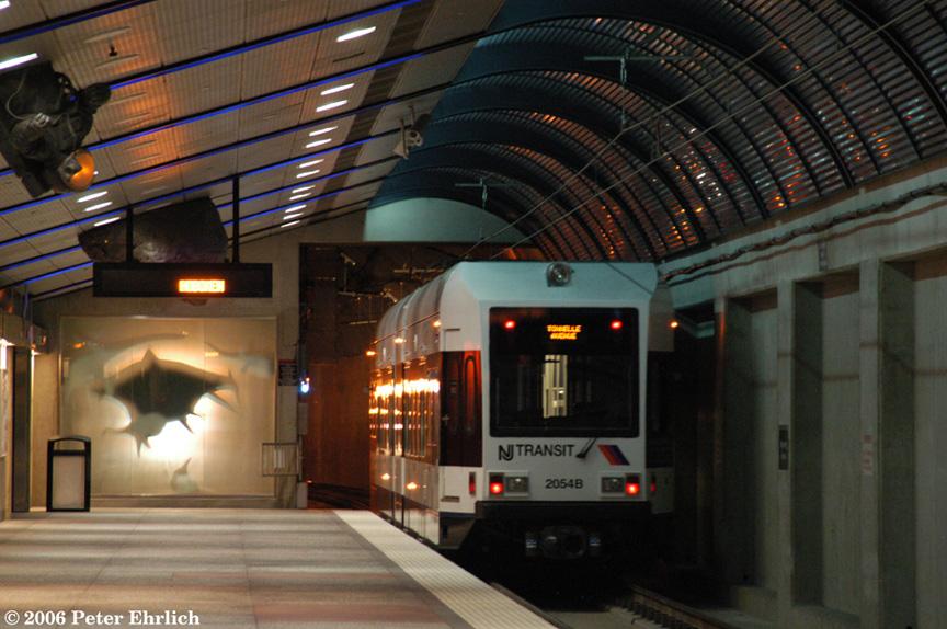 (213k, 864x574)<br><b>Country:</b> United States<br><b>City:</b> Union City, NJ<br><b>System:</b> Hudson Bergen Light Rail<br><b>Location:</b> Bergenline Avenue <br><b>Car:</b> NJT-HBLR LRV (Kinki-Sharyo, 1998-99)  2054 <br><b>Photo by:</b> Peter Ehrlich<br><b>Date:</b> 9/28/2006<br><b>Notes:</b> Showing artwork consisting of an illusion of swimming sharks.<br><b>Viewed (this week/total):</b> 0 / 1985