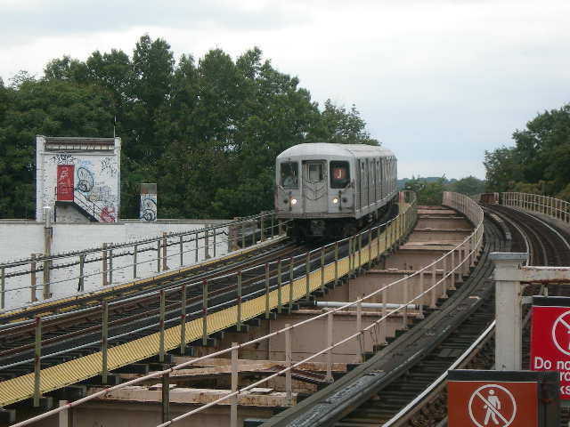(80k, 640x480)<br><b>Country:</b> United States<br><b>City:</b> New York<br><b>System:</b> New York City Transit<br><b>Line:</b> BMT Nassau Street/Jamaica Line<br><b>Location:</b> 102nd-104th Streets <br><b>Photo by:</b> Joe Grillo<br><b>Date:</b> 9/10/2006<br><b>Notes:</b> J eastbound pulling into 104th street BMT station. The tall trees to the left is the old Brooklyn Manor LIRR right of way and station.<br><b>Viewed (this week/total):</b> 0 / 2446