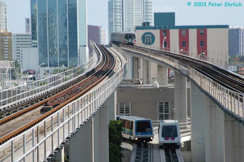 (162k, 792x526)<br><b>Country:</b> United States<br><b>City:</b> Miami, FL<br><b>System:</b> Miami Metromover<br><b>Location:</b> Government Center <br><b>Car:</b>  2/25 <br><b>Photo by:</b> Peter Ehrlich<br><b>Date:</b> 4/25/2003<br><b>Notes:</b> Two cars pass south of Government Center Station.  Southbound Metrorail train in background.<br><b>Viewed (this week/total):</b> 2 / 2870