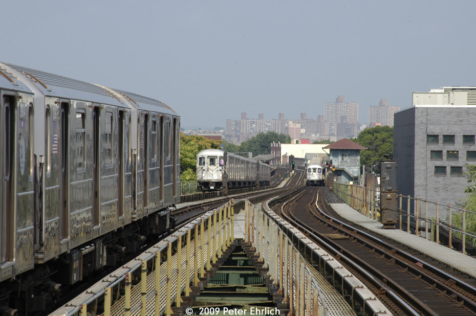(203k, 930x618)<br><b>Country:</b> United States<br><b>City:</b> New York<br><b>System:</b> New York City Transit<br><b>Line:</b> IRT Flushing Line<br><b>Location:</b> Junction Boulevard <br><b>Route:</b> 7<br><b>Car:</b> R-62A (Bombardier, 1984-1987)  2064 <br><b>Photo by:</b> Peter Ehrlich<br><b>Date:</b> 7/22/2009<br><b>Notes:</b> Outbound. With inbound local approaching Junction Blvd., and an outbound local at 103rd Street in the background.<br><b>Viewed (this week/total):</b> 0 / 1041