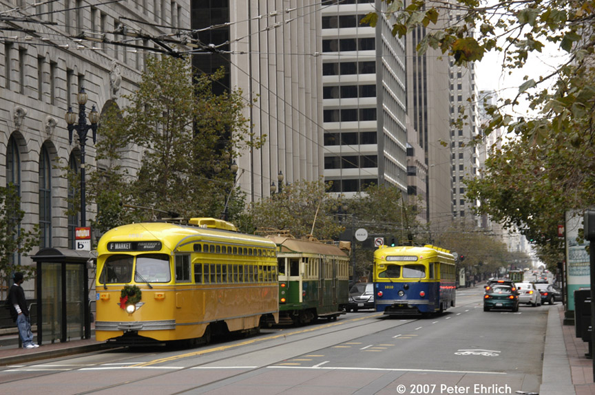 (235k, 864x574)<br><b>Country:</b> United States<br><b>City:</b> San Francisco/Bay Area, CA<br><b>System:</b> SF MUNI<br><b>Location:</b> Market/Main <br><b>Car:</b> SF MUNI PCC (Ex-SEPTA) (St. Louis Car Co., 1947-1948)  1052 <br><b>Photo by:</b> Peter Ehrlich<br><b>Date:</b> 11/25/2007<br><b>Notes:</b> Market/Main inbound. With 496 (Melbourne W2) inbound, and 1010 (Muni 1939 blue/gold) outbound.<br><b>Viewed (this week/total):</b> 0 / 579