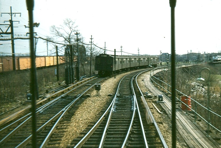 (125k, 749x500)<br><b>Country:</b> United States<br><b>City:</b> New York<br><b>System:</b> New York City Transit<br><b>Line:</b> BMT Myrtle Avenue Line<br><b>Location:</b> Metropolitan Avenue <br><b>Car:</b> BMT Multi  <br><b>Photo by:</b> Brian J. Cudahy<br><b>Date:</b> 1956<br><b>Notes:</b> Multi-section unit heads into Metropolitan Avenue with NY Connecting RR freight on its right, as photographed from a BU open-gate car.<br><b>Viewed (this week/total):</b> 2 / 2793