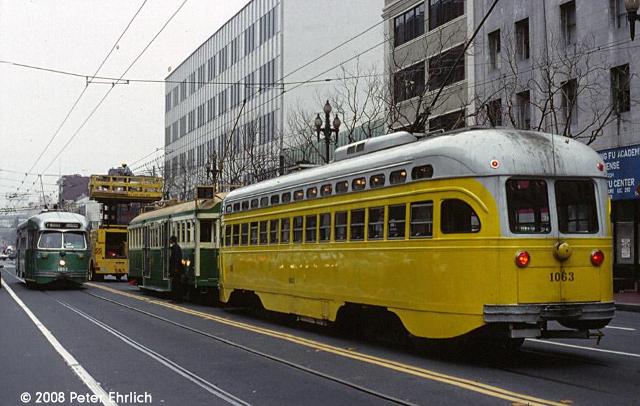 (223k, 930x590)<br><b>Country:</b> United States<br><b>City:</b> San Francisco/Bay Area, CA<br><b>System:</b> SF MUNI<br><b>Location:</b> Market/11th <br><b>Car:</b> SF MUNI PCC (Ex-SEPTA) (St. Louis Car Co., 1947-1948)  1055 <br><b>Photo by:</b> Peter Ehrlich<br><b>Date:</b> 2/7/1996<br><b>Notes:</b> Inbound.  With 496 (Melbourne) and 1063 (Baltimore) outbound, blocked by overhead line truck.<br><b>Viewed (this week/total):</b> 0 / 367