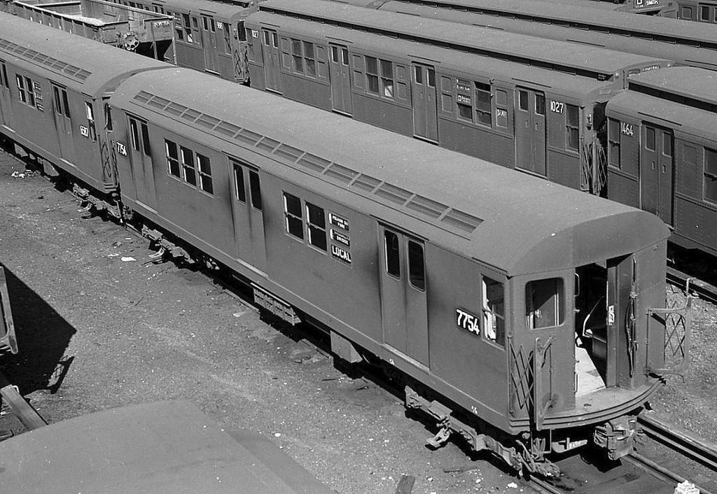 (189k, 1044x726)<br><b>Country:</b> United States<br><b>City:</b> New York<br><b>System:</b> New York City Transit<br><b>Line:</b> IRT White Plains Road Line<br><b>Location:</b> East 180th Street <br><b>Route:</b> Work Service<br><b>Car:</b> Hi-V  <br><b>Photo by:</b> Joel Shanus<br><b>Notes:</b> Train of three Hedley Hi-V manual door motors towing IRT hopper cars; NYW&B line at left. Circa 1954.<br><b>Viewed (this week/total):</b> 3 / 1998