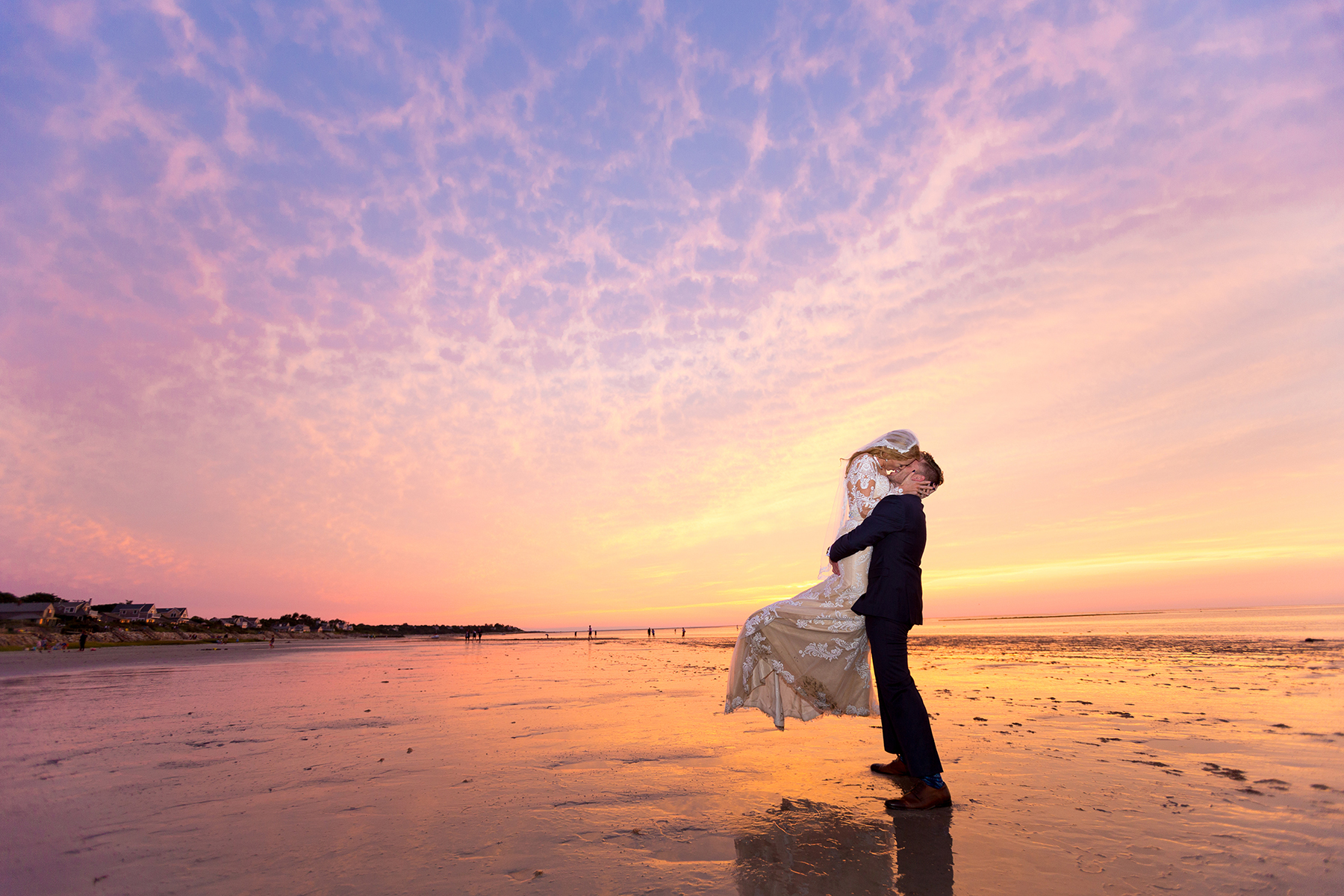 Groom and bride kissing on Cape Cod beach at sunset