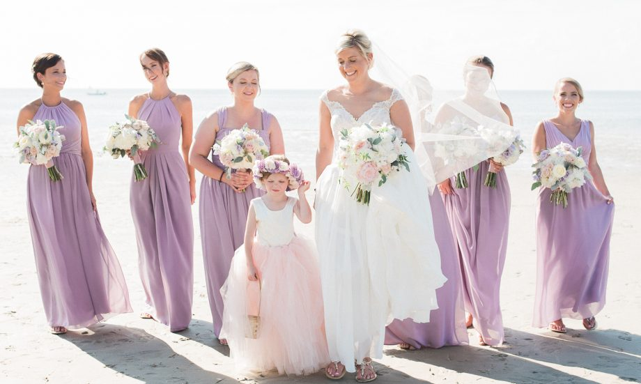 Bride and bridesmaids and flower girl on Cape Cod beach