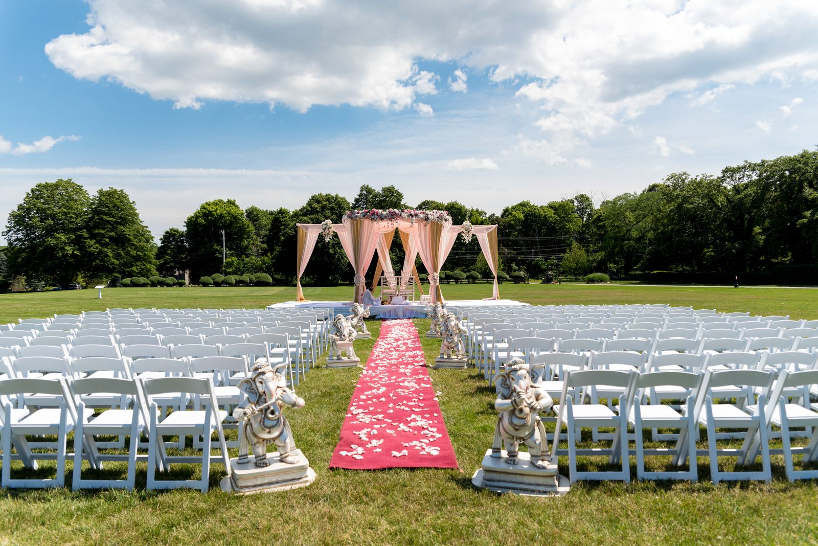 Wedding aisle and seating on front lawn, with petals on aisle carpet