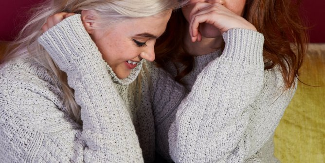 Girls in matching gray knitted sweaters smiling