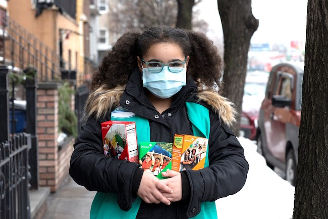 A Girl Scout holds cookies