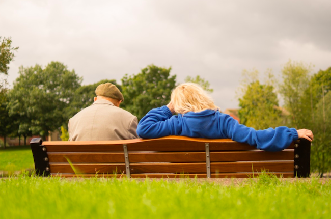 two old people on a bench with a life insurance policy