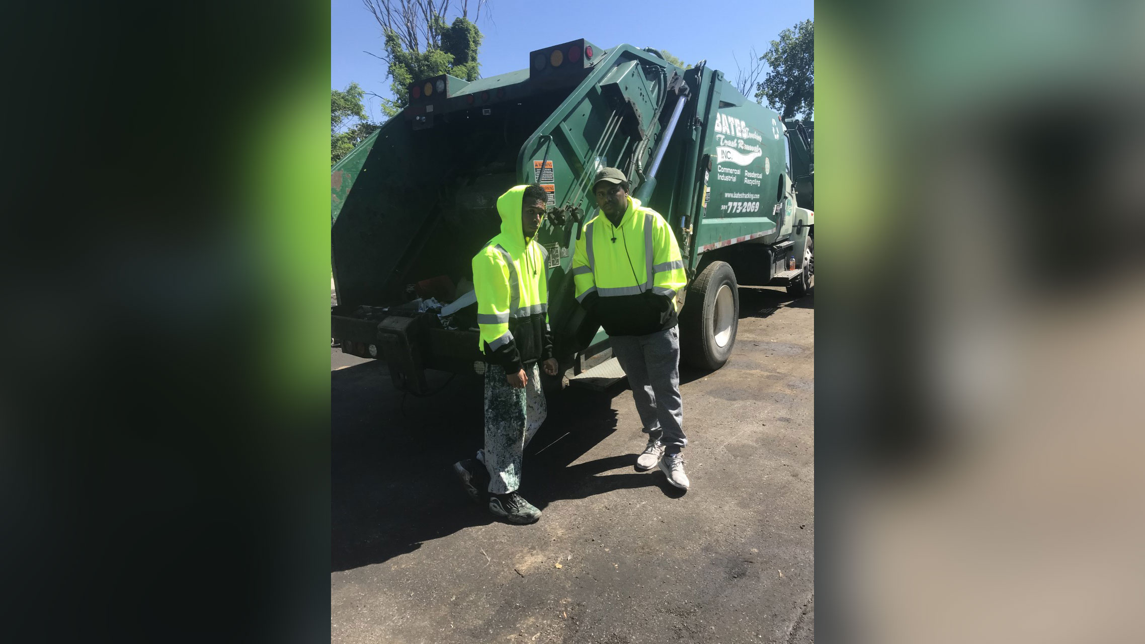 Two people in front of a garbage truck