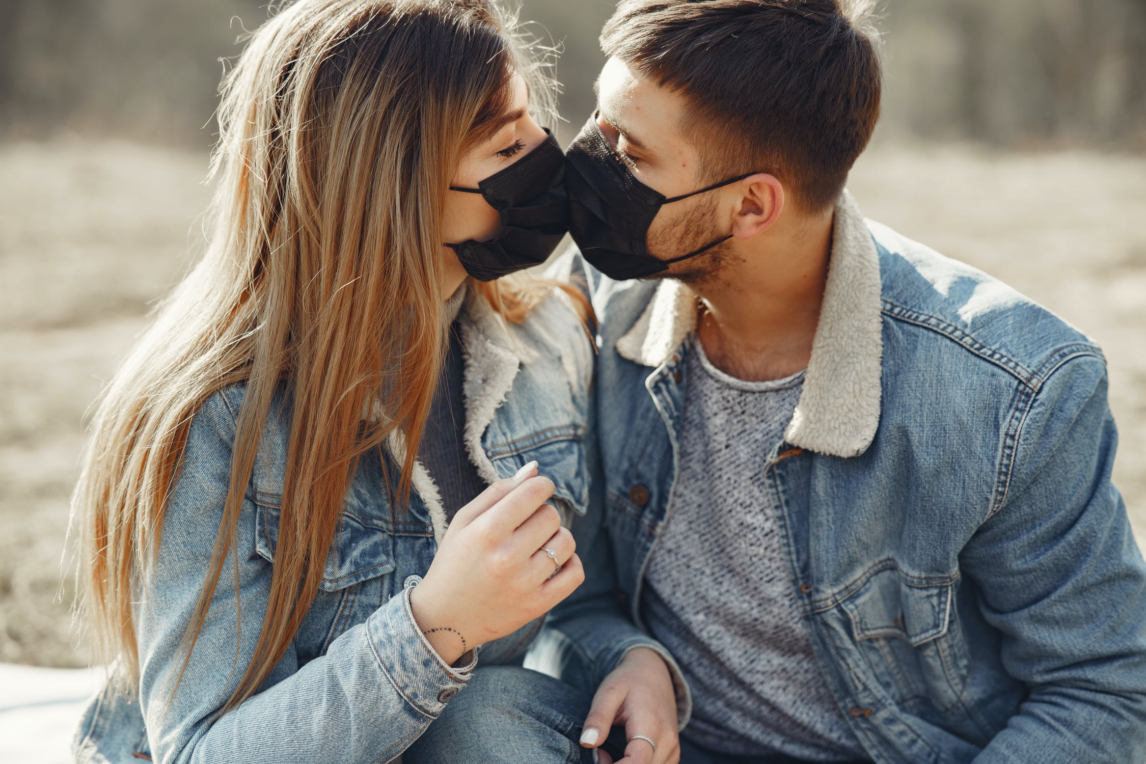 couple kisses with masks