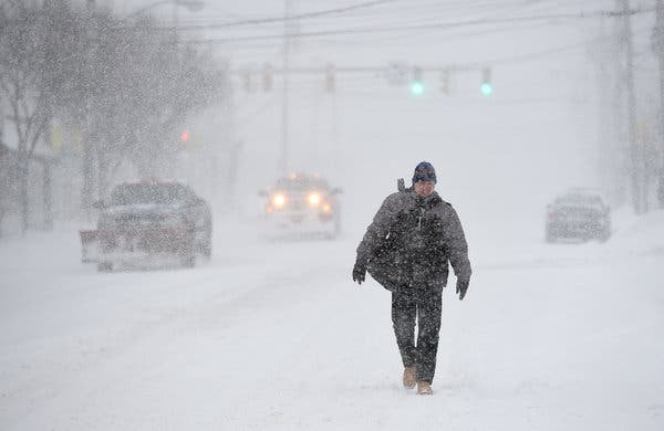 man walking in blizzard