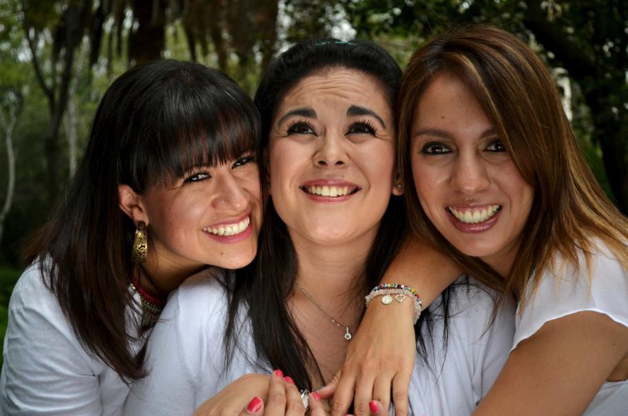 three smiling female friends