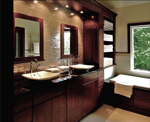 This contemporary spa bathroom design idea with clean lines was created by Gary Tilson. It features pocket doors, a hamper base cabinet and Milan tub surround