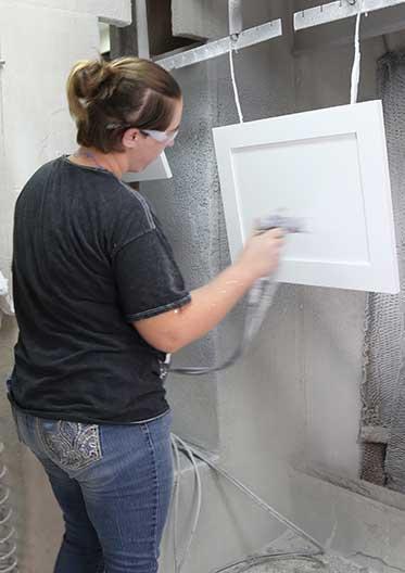 Hand spraying final coats on doors
