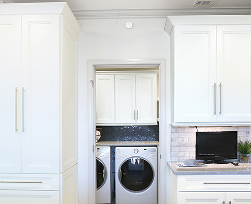 Laundry room  / Utility room enter door is flanked with Maple Cabinets with a Glacier White painted finish topped with a Pewter Glaze.