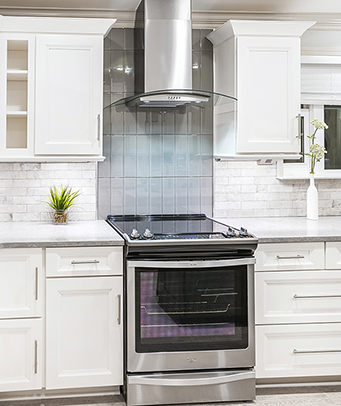 Chelsea Cabinetry with under wall cabinet lighting and a beautiful Stainless Vent Hood and Gray / Green backsplash tile
