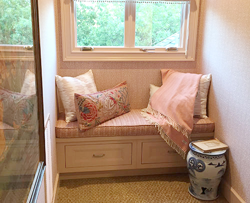 The comfortable window bench in this photo is a mixture of pink and whites. Creating a haven to read, talk or just chill in the sunshine.