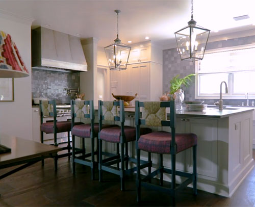 View of the Gray breakfast bar / 4 seat dining island. Wall to ceiling gray cabinetry is seen in the corner of the kitchen.