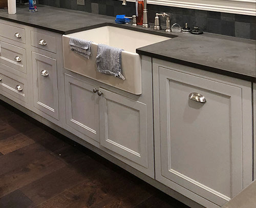 Next to the Apron Front Base Cabinet with a large farmhouse sink installed is a Super Capacity Wastebasket Base Cabinet.