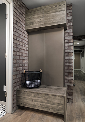 A charming small Mudroom consisting of a storage bench and a high storage cabinet greets you as you enter