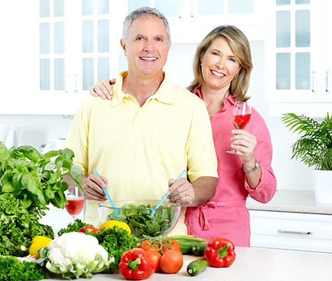Older Man and Woman relaxed and preparing a salad on their kitchen Island