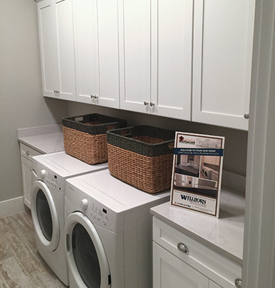 Laundry room features white MDF Hancock Shaker cabinetry