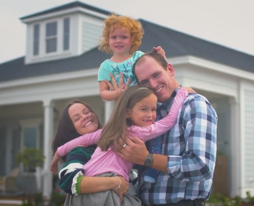 The Brooking family in front of their new mortgage free home.