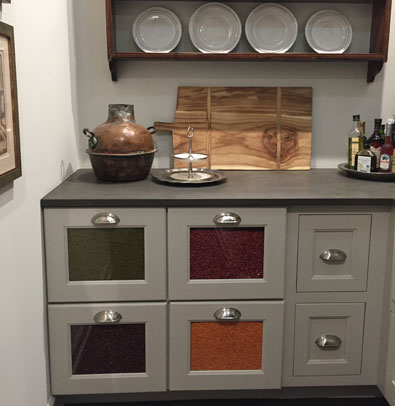 The pantry has a beautiful gray four drawer glass front base cabinetry with a pop of color showing in the glass openings �