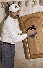 Hand rubbing stained door to enhance its wood grain.