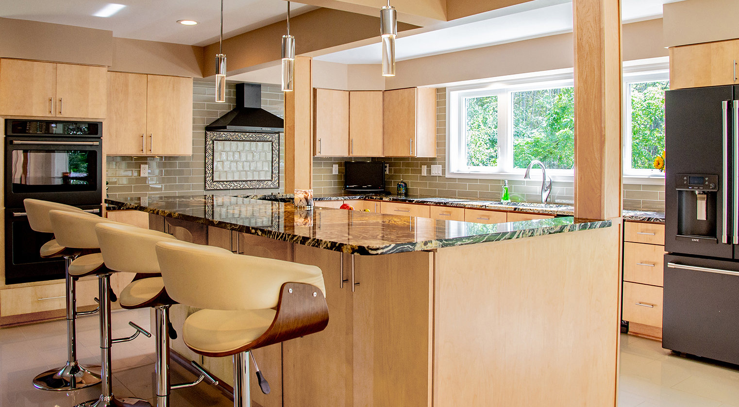 The Kitchen design expanded the room for entertaining. The owner also wanted large windows to bring in more sunlight and a large island with a breakfast bar.