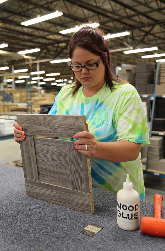 Photo of female employee assembling 5 piece cabinet door