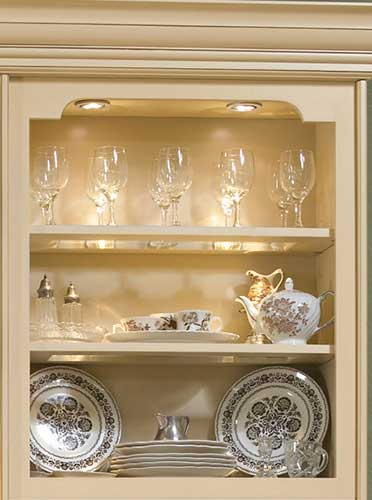 An eye catching Open Display Cabinet with accent lighting illuminating glassware, china and decorative serving pieces.