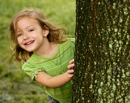 Photo of a small girl smiling as she hides behind a large tree. 