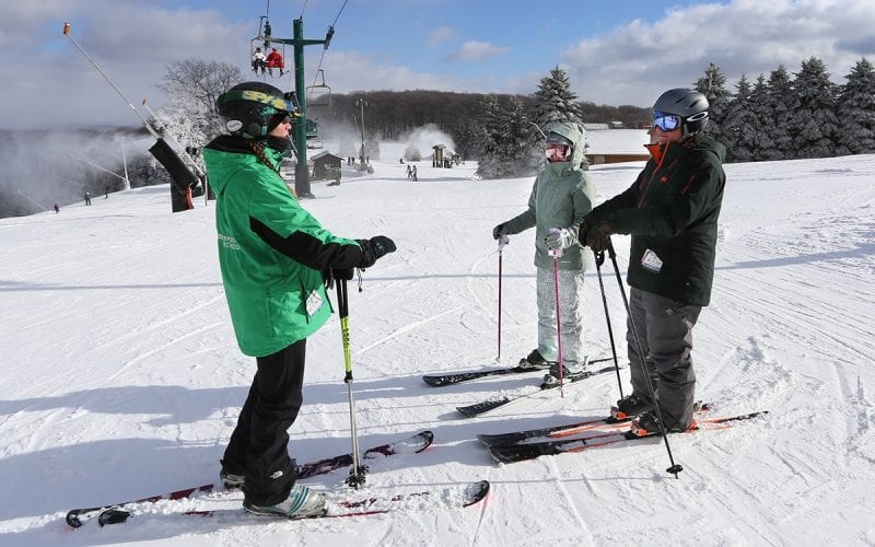 Adults taking a ski lesson