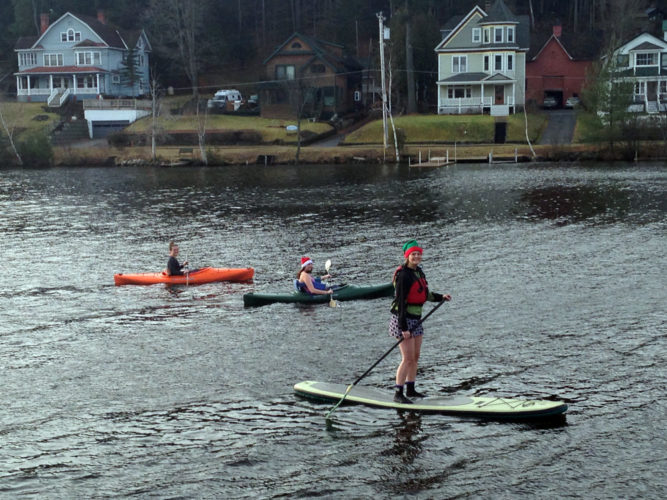 Trish Wickwire, right, uses a paddleboard and two other women kayak on unfrozen Lake Flower, Saranac Lake, on Christmas Eve, 2015. (Enterprise photo — Catherine Moore)