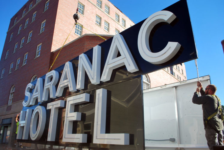 The Hotel Saranac's new rooftop sign is hoisted up the side of the building on Academy Street in September. (Enterprise photo — Chris Knight)