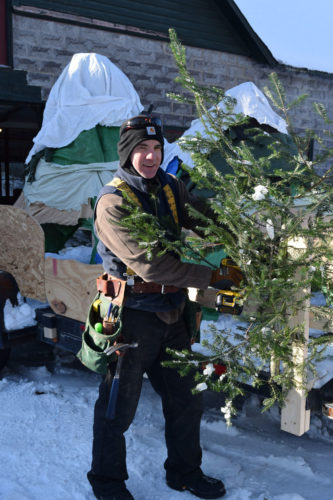"""Northern Lights School parent and board member Michael Williams attaches a tree to the school's """"mountain mosaic"""" float for today's Saranac Lake Winter Carnival Gala Parade. (Enterprise photo — Chris Knight)"""